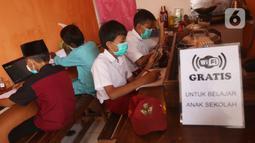 Sejumlah siswa sekolah dasar belajar dengan menggunakan wifi gratis yang disediakan oleh warkop Rizki, di Pondok Aren, Tangerang Selatan, Rabu (29/7/2020). Wifi gratis disediakan untuk membantu anak anak sekitar yang tidak memiliki jaringan internet dan smartphone. (Liputan6.com/Angga Yuniar)