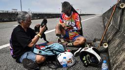 Longboarder dan penderita kanker Nongluck Chairuettichai, juga dikenal sebagai Jeab, dengan putranya Soteera selama sesi latihan di Bangkok pada 9 September 2020. Kegiatan ini dilakukan Jeab yang berusia 63 tahun sebagai jalan pemulihan dari kanker payudara yang dideritanya (Lillian SUWANRUMPHA/AFP)