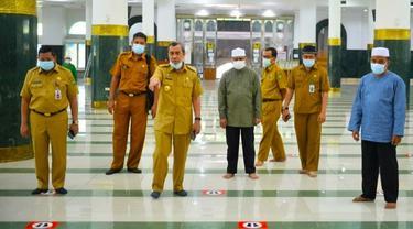 Gubernur Riau Syamsuar mengecek pengaturan jarak untuk salat berjamaah di masjid.