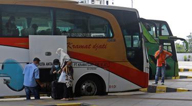Petugas memasukkan barang bawaan penumpang ke dalam bagasi bus di Terminal Terpadu Pulo Gebang, Jakarta, Kamis (11/2/2021). Berdasarkan data Dishub hingga pukul 14.00 WIB, Terminal Terpadu Pulo Gebang telah memberangkatkan 466 pemudik menuju luar Jakarta. (Liputan6.com/Herman Zakharia)