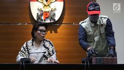 Wakil Ketua KPK, Basaria Panjaitan (kiri) bersama petugas KPK menunjukkan barang bukti hasil OTT terkait pengisian jabatan perangkat daerah di lingkungan Pemkab Kudus, Gedung KPK Jakarta, Sabtu (27/7/2019). KPK menyita barang bukti uang sebesar Rp170 juta. (Liputan6.com/Helmi Fithriansyah)