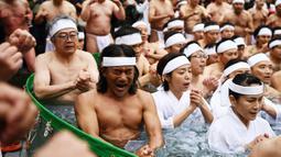 Orang-orang percaya Shinto dari Kuil Teppozu Inari mandi dengan air dingin untuk menyucikan jiwa dan tubuh mereka selama ritual Tahun Baru di Tokyo, Minggu (12/1/2020). Sekitar 100 orang percaya Shinto ambil bagian dalam ritual tahunan tersebut. (AFP/Charly Triballeau)