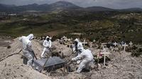 Pekerja mengenakan alat pelindung diri saat mengubur korban meninggal akibat virus corona COVID-19 di pabrik semen No. 13 di Tijuana, Baja California, Meksiko, 21 April 2020. (Photo by Guillermo Arias/AFP)