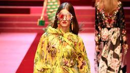 Seorang model berjalan membawa tas besar mirip tas pasar berisi sayuran untuk koleksi Dolce & Gabbana Spring/Summer 2018 pada Milan Fashion Week, Minggu (24/9). Tas pasar itu memiliki motif plaid dengan pinggiran warna kuning. (AFP PHOTO / Andreas SOLARO)