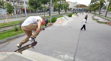 Seorang pria bermain papan luncur atau skateboard di sebuah taman olahraga jalanan di Wina, Austria, pada 8 Juli. Sejumlah orang di ibu kota Austria, Wina, pergi ke taman olahraga jalanan untuk melakukan olahraga luar ruangan setelah pembatasan COVID-19 dicabut. (Xinhua/Georges Schneider)