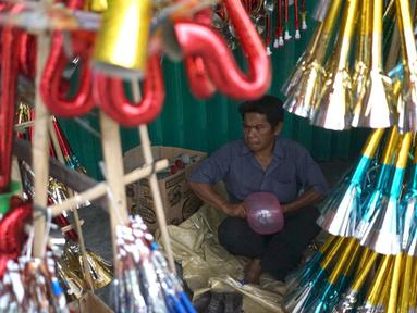Pedagang terompet menunggu calon pembeli di kawasan Glodok, Jakarta, Jumat (27/12/2019). Menjelang perayaan Tahun Baru 2020, penjual terompet musiman mulai marak di sejumah kawasan dengan harga jual berkisar Rp5ribu hingga Rp15ribu tergantung model. (Liputan6.com/Immanuel Antonius)