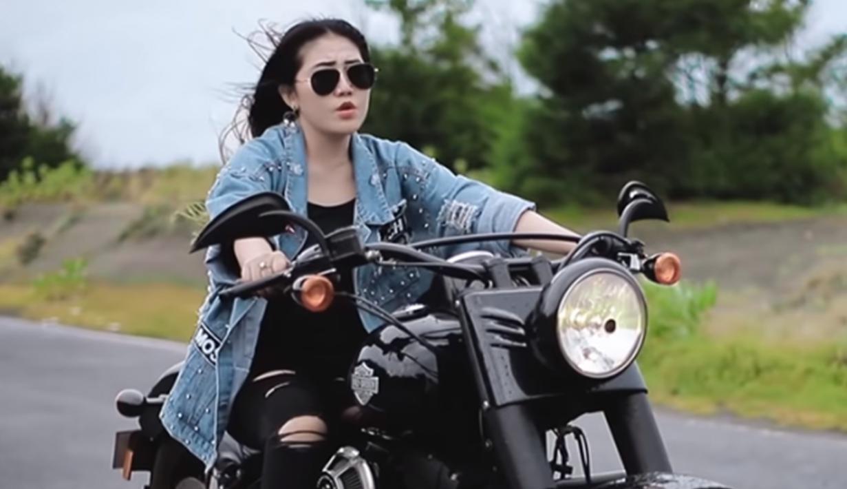 Dengan outfit hitam dibalut outer denim, gaya Via Vallen saat naik motor gede atau mode sukses bikin penggemar terpesona. (Liputan6.com/YouTube/Via Vallen)