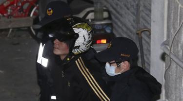 Pelaku pemenggal bocah perempuan (tengah) diamankan polisi ke Pusat Penahanan Taipei, Taiwan, Selasa (29/3). Pria itu memenggal kepala bocah tiga tahun dengan menggunakan pisau daging di hadapan ibu kandung bocah tersebut. (REUTERS/Tony HuangTAIWAN OUT)