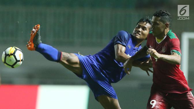 Pemain depan Timnas Indonesia U-23, Alberto Goncalves (kanan) berebut bola dengan pemain Thailand U-23, Saringkan Promsupa pada laga persahabatan di Stadion Pakansari, Kab Bogor, Minggu (3/6). Laga berakhir imbang 0-0. (Liputan6.com/Helmi Fithriansyah)