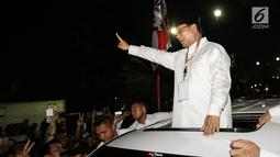 Calon Presiden Prabowo Subianto menyapa pendukungnya di sepanjang jalan Imam Bonjol usai pengambilan nomor urut di Gedung KPU Jakarta, Jumat (21/9). Prabowo memberikan salam 2 jari dengan mobil warna putih. (Liputan6.com/Fery Pradolo)