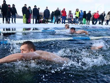 Peserta saat mengikuti kompetisi renang musim dingin tahunan dengan air es beku di Trakai, Lituania (24/2). Para peserta tetap antusias mengikuti lomba walaupun dengan suhu di luar hingga minus 12 derajat Celcius. (AFP Photo/Petras Malukas)