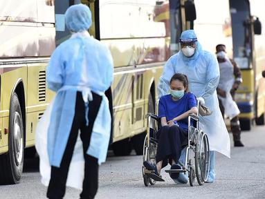 Petugas membawa warga Malaysia menggunakan kursi roda saat tiba setelah dievakuasi dari Wuhan, China akibat virus corona di Bandara Internasional Kuala Lumpur di Sepang, Selasa, (4/2/2020). Sejumlah 107 warga Malaysia dievakuasi Wuhan, China. (Muzzafar Kasim/Malaysia's Ministry of Health/AFP)