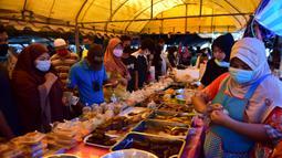 Orang-orang berbelanja di pasar makanan pada hari pertama bulan suci Ramadhan di provinsi Narathiwat di Thailand selatan (24/4/2020). Sejumlah pedagang menjual berbagai makanan selama bulan suci Ramadan di pasar tersebut. (AFP/Madaree Tohlala)