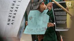 Seorang mahasiswa membawa poster saat menggelar aksi di depan Gedung KPU, Jakarta, Selasa (23/4). Dalam Aksi #Mahasiswakawalkpu tersebut mendesak KPU RI segera menyelesaikan permasalahan pemilu. (Liputan6.com/Faizal Fanani)