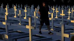 Seorang pria berjalan dekat kuburan tentara yang tewas dalam invasi Turki ke Siprus di pemakaman militer Tymvos Macedonitissas, Nicosia, Siprus, Senin (20/7/2020). Ribuan orang Yunani dan tentara Siprus tewas selama invasi Turki ke Pulau Siprus pada tahun 1974. (AP Photo/Petros Karadjias)