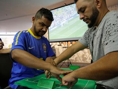 Suporter Brasil yang buta dan tuli, Carlos Junior merasakan berlangsungnya pertandingan 16 besar Piala Dunia 2018 antara Brasil melawan Meksiko dibantu penerjemah dengan miniatur lapangan sepak bola di Sao Paulo, Brasil, (2/7). (AP Photo / Nelson Antoine)