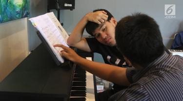 Seorang anak berkebutuhan khusus mendengarkan instruktur saat latihan piano di Daya Pelita Kasih Center, Pejaten, Jakarta, Kamis (24/5). Tempat pelatihan piano ini dipimpin oleh pianis Ananda Sukarlan. (Liputan6.com/Arya Manggala)