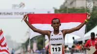 Pelari Indonesia Agus Prayogo membawa Bendera Merah Putih usai melakukan trek maraton SEA Games XXIX di di Putrajaya, Kuala Lumpur, Malaysia, Sabtu (19/8). Agus berhasil meraih medali perak nomor lari marathon cabang atletik. (Liputan6.com/Faizal Fanani)