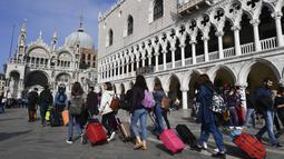 Turis berjalan di sepanjang Doge's Palace menuju Basilika Santo Markus di Venesia (4/11/2019). Kota ini memiliki luas wilayah 412 km² dan populasi 271.663 jiwa (2003). (AFP Photo/Miguel Medina)
