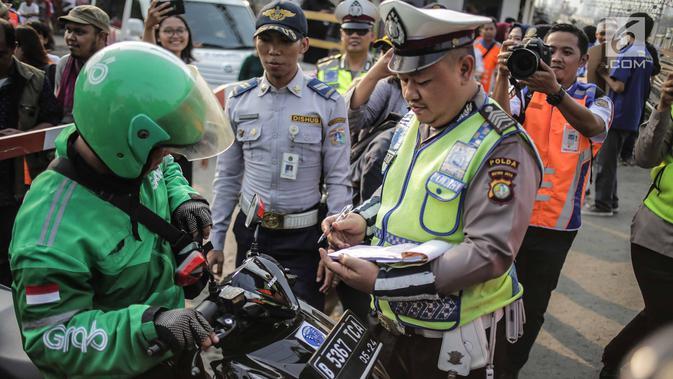 Polisi menilang pengendara saat petugas PT KAI Daop I menggelar sosialisasi tertib berlalu lintas di pintu perlintasan sebidang kawasan Bukit Duri, Jakarta, Selasa (17/9/2019). Sosialisasi dilakukan karena banyaknya kecelakaan akibat ketidakdisiplinan pengendara. (Liputan6.com/Faizal Fanani)