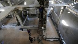 Seniman Belanda, Marjan Teeuwen (bawah) berdiskusi dengan asistennya saat menyelesaikan sebuah karya arsitektur dari reruntuhan rumah yang hancur bekas perang pada 2014 di Khan Younis, selatan Jalur Gaza, 12 November 2016. (REUTERS/Ibraheem Abu Mustafa)