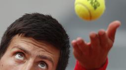 Ekspresi wajah petenis Serbia, Novak Djokovic melakukan servis saat melawan petenis Spanyol, Jaume Munar pada ajang Prancis Terbuka 2018 di Roland Garros stadium, Paris, France, (30/5/2018). (AP/Christophe Ena)