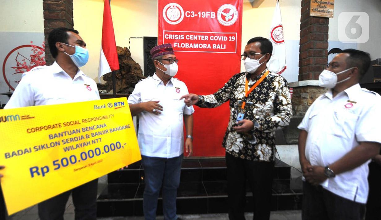 Direktur Utama PT Bank Tabungan Negara (Persero) Tbk. Haru Koesmahargyo (kedua kanan) menyerahkan secara simbolis bantuan CSR senilai Rp500 juta kepada Ketua Ikatan Keluarga Besar (IKB) masyarakat NTT-Flobamora yang berada di Denpasar, Bali, Jumat (09/04/2021). (Liputan6.com/Pool/BTN)