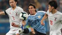 Striker Uruguay, Edinson Cavani berusaha melewati dua pemain Jepang, Takehiro Tomiyasu dan Gaku Shibasaki selama pertandingan grup C Copa America 2019 di Arena Gremio di Porto Alegre, Brasil (20/6/2019). Jepang bermain imbang 2-2 atas Uruguay. (AP Photo/Silvia Izquierdo)