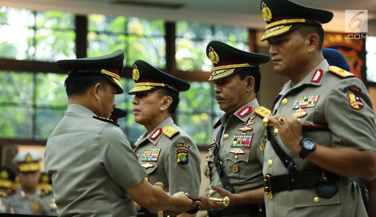 Kapolri Jenderal Tito Karnavian menyerahkan tongkat komando kepada Irjen Idham Aziz dalam acara sertijab di Rupatama Mabes Polri, Rabu (26/7). Idham Aziz resmi menjabat Kapolda Metro Jaya menggantikan Irjen Mochamad Iriawan (Liputan6.com/Faizal Fanani)