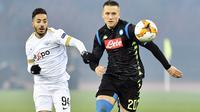 Pemain Napoli, Piotr Zielinski, berebut bola dengan pemain FC Zurich, Salim Khelifi, pada laga Liga Europa di Stadion Letzigrund, Kamis (14/2). Napoli menang 3-1 atas FC Zurich. (AP/Walter Bieri)