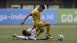 Striker Bhayangkara FC, Ramiro Ezequiel, berebut bola dengan pemain Persebaya pada laga Shopee Liga 1 di Stadion Patriot Chandrabhaga, Bekasi, Sabtu (31/8). Persebaya menang 2-0 atas Bhayangkara. (Bola.com/Yoppy Renato)