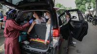 Petugas menyuntikkan vaksin COVID-19 kepada warga saat pelaksanaan vaksinasi secara drive-thru di Mapolres Jakarta Selatan, Selasa (29/6/2021). Layanan ini dilakukan untuk mempercepat vaksinasi COVID-19 kepada warga. (Liputan6.com/Faizal Fanani)