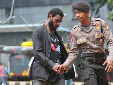 Mahasiswa Papua berjabat tangan dengan seorang polisi saat mendatangi Polda Metro Jaya, Jakarta, Selasa (1/12/2015). Kedatangan mereka untuk menunggu teman mereka yang diperiksa polisi (Liputan6.com/Yoppy Renato)