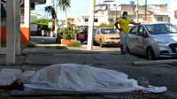 Seorang pria melihat ke arah jenazah yang tergeletak selama tiga hari di luar sebuah klinik di Guayaquil, Ekuador, Jumat (3/4/2020). Di Guayaquil, banyak dijumpai jenazah korban virus corona COVID-19 yang terlantar di jalanan. (Str/Marcos Pin/AFP)