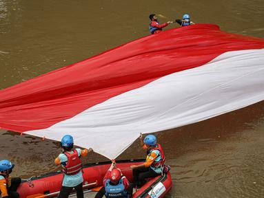 Sejumlah relawan membentangkan bendera Merah Putih di aliran kali Ciliwung di kawasan Sudirman, Jakarta, Minggu (22/8/2021). Pembentangan atau pengibaran bendera Merah Putih tersebut dilaksanakan untuk memperingati HUT ke-76 RI. (Liputan6.com/Faizal Fanani)