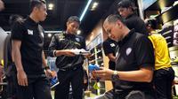 Iwan Budianto saat masih menjabat sebagai CEO Arema tengah melihat-lihat sepatu pilihan para pemainnya sebelum memborong begitu banyak sepatu untuk pemain dan ofisial Arema saat berada di Kuala Lumpur, Malaysia, pada 2014 silam. (Bola.com/Iwan Setiawan)