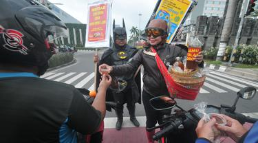 Warga mengenakan kostum superhero Gundala dan Batman menawarkan Jamu saat melakukan aksi sosialisasi pencegahan virus corona di Solo, Rabu (4/3/2020). Indonesia pada 2 Maret melaporkan kasus pertama virus corona yang menimpa dua warga Depok, Jawa Barat. (AFP Photo/Anwar Mustafa)