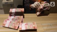 Teller menghitung mata uang Rupiah di Jakarta, Kamis (16/7/2020). Rupiah secara point to point pada triwulan II 2020 mengalami apresiasi 14,42 persen. (Liputan6.com/Angga Yuniar)