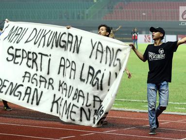 Suporter tim Maung Bandung membentangkan spanduk usai menyaksikan laga Bhayangkara FC melawan Persib di Stadion Patriot Candrabhaga, Bekasi, Minggu (4/6). Persib kalah 0-2 dari Bhayangkara FC. (Liputan6.com/Helmi Fithriansyah)