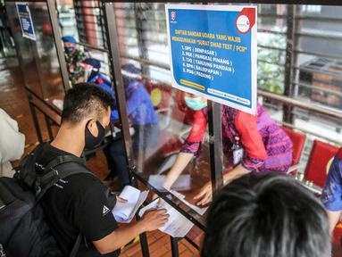 Petugas memeriksa dokumen kesehatan calon penumpang sebelum melakukan lapor diri (chek in) di Terminal 2 Bandara Soekarno Hatta, Tangerang, Banten, Rabu (10/6/2020). PT Angkasa Pura II selaku pengelola mulai menjalankan skenario protokol penerapan tatanan normal baru. (Liputan6.com/Faizal Fanani)