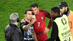 Seorang penggemar masuk lapangan dan mengajak berfoto Cristiano Ronaldo seusai laga Portugal melawan Austria pada laga kedua Grup F Piala Eropa 2016di Parc des Princes, Minggu (19/6/2016) dini hari WIB. (AFP/Miguel Medina)