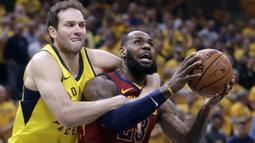 Pemain Cleveland Cavaliers, LeBron James (kanan) dilanggar pemain Indiana Pacers, Bojan Bogdanovic pada game keenam playoffs NBA basketball di Bankers Life Fieldhouse, Indianapolis, (27/4/2018). Pacers menang 121-87. (AP/Darron Cummings)