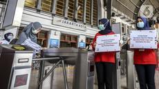 Petugas menunjukkan pesan peringatan COVID-19 di Stasiun Jakarta Kota, Jakarta, Rabu (28/10/2020). Mengantisipasi lonjakan penumpang saat cuti bersama dan Sumpah Pemuda, PT KCI mengajak pengguna KRL bersatu dan bangkit melawan COVID-19 dengan menerapkan 3M. (Liputan6.com/Johan Tallo)