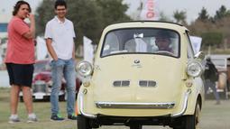 Seorang pria mengendarai mobil model BMW Isetta kuning klasik selama pertemuan klasik Kairo ke-7 di Kairo, Mesir (23/3). Pertemuan ini menjadi ajang nostalgia bagi para pecinta mobil klasik. (Reuters/Mohamed Abd El Ghany)