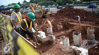 Pekerja mencangkul tanah di proyek pembangunan jalur LRT seksi Cawang-Cibubur, Jakarta, Kamis (8/12). Jalur LRT ini nantinya akan digunakan sebagai salah satu transportasi dalam pelaksanaan Asian Games 2018 .(Liputan6.com/Faizal Fanani)