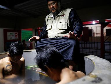 Ustad Ahmad Ischsan Maulana mengobati dua pasien yang berendam dalam bak berisi ramuan herbal di Purbalingga, Jateng, 27 Juli 2016. Terapi untuk pecandu narkoba ini dilakukan dengan merebus pasien di atas kompor yang menyala. (REUTERS/Darren Whiteside)