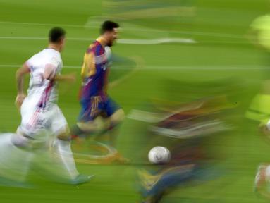 Striker Barcelona, Lionel Messi, menggiring bola melewati pemain Real Valladolid pada laga Liga Spanyol di Stadion Camp Nou, Selasa (6/4/2021). Barcelona menang dengan skor 1-0. (AP Photo/Joan Monfort)