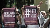 Massa dari HTI membentangkan poster saat menunggu putusan sidang gugatan di luar Gedung Pengadilan Tata Usaha Negara (PTUN), Jakarta, Senin (7/5). (Merdeka.com/Iqbal S Nugroho)