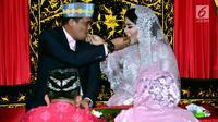 Putri Presiden Joko Widodo, Kahiyang Ayu dan Muhammad Bobby Afif Nasution saling menyuapi saat prosesi Mangalehan Marga, Boru Siregar, di rumah paman Bobby di Medan, Selasa (21/11). (Liputan6.com/Pool/Media Center)