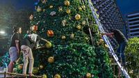 Pekerja menyelesaikan pembuatan Pohon Natal di Thamrin 10, Jakarta, Selasa (22/12/2020). Pohon Natal akan dipasang pada 23 Desember hingga 1 Januari mendatang. (Liputan6.com/Faizal Fanani)